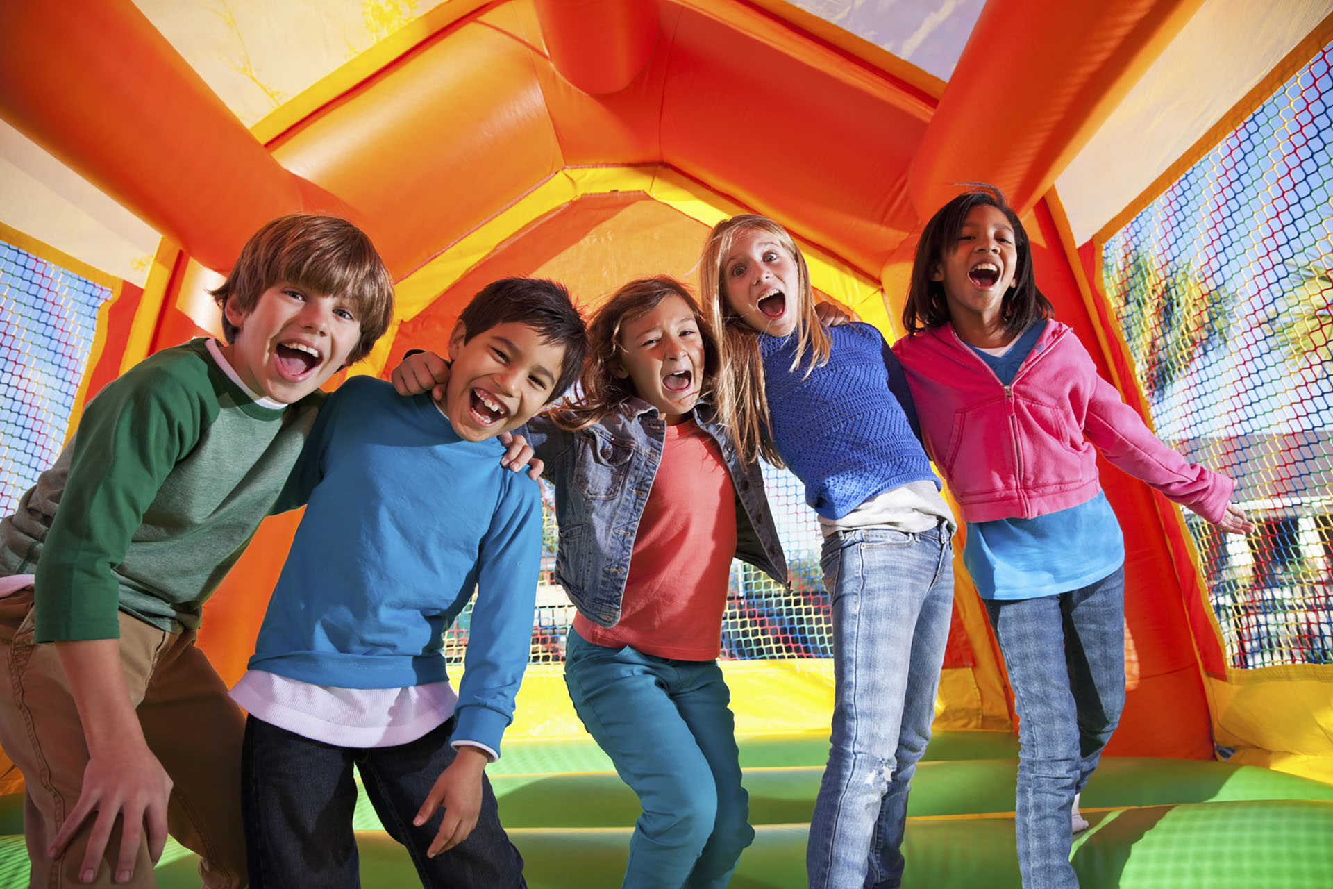group of kids playing insde bouncy castle enclosure