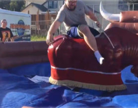 Man riding mechanical bull in inflatable arena